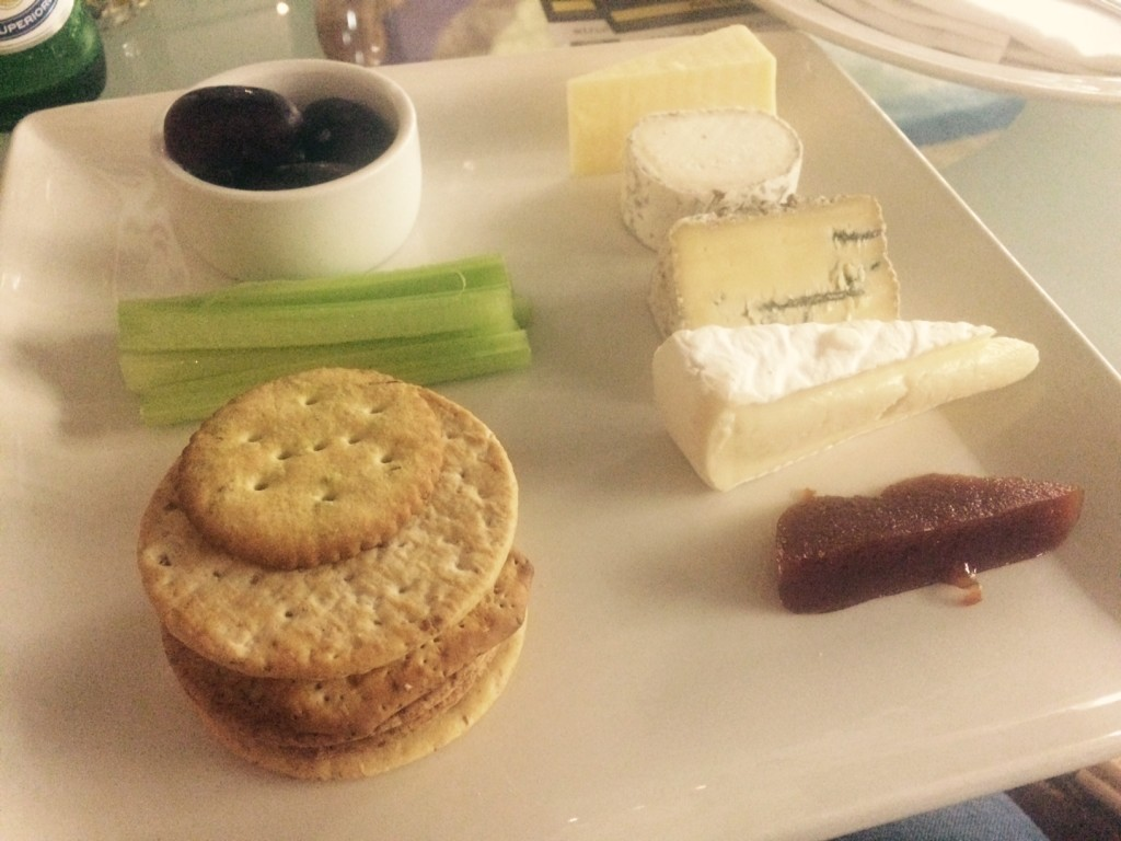 A selection of cheeses, crackers, grapes, quince jelly and celery on a plate