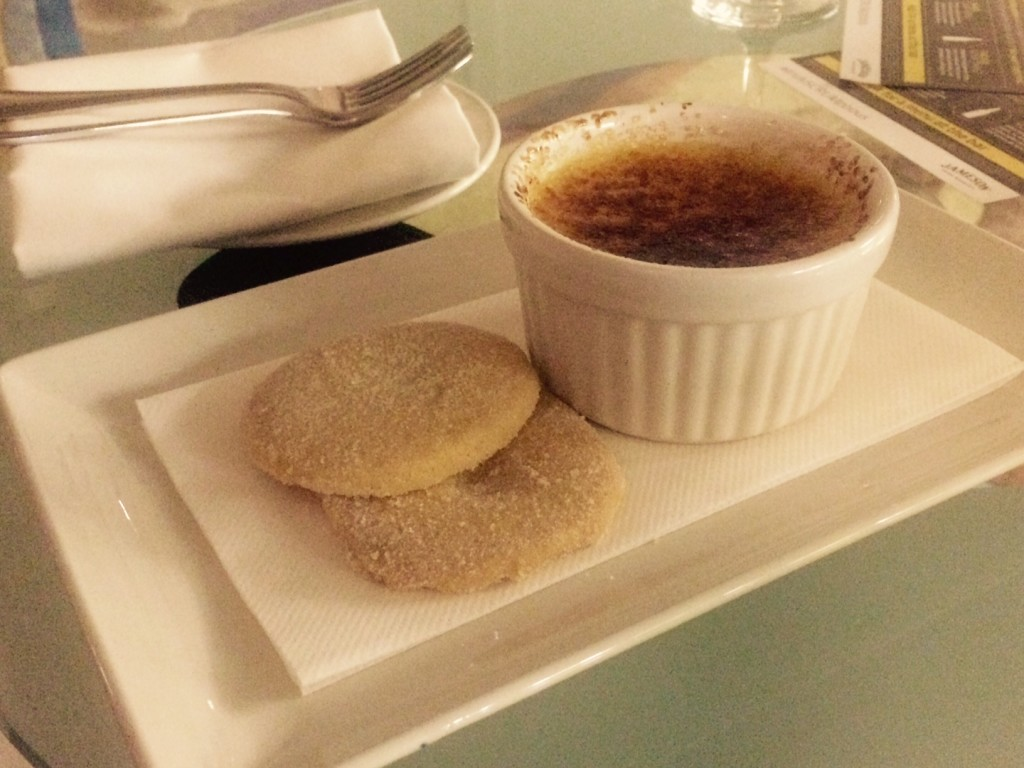 Creme brulee in a ramekin served alongside two shortbread biscuits