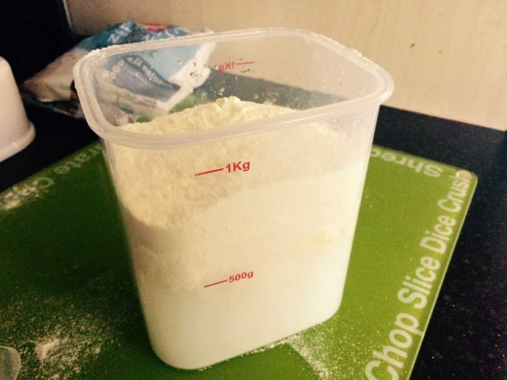A plastic tub filled with water and yoghurt mix, not yet stirred