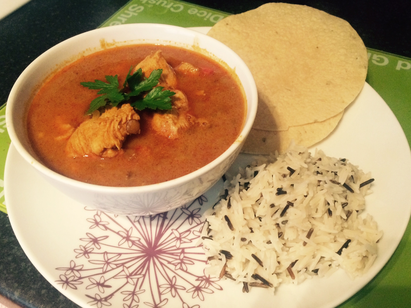 A bowl of curry with wild rice and poppadoms