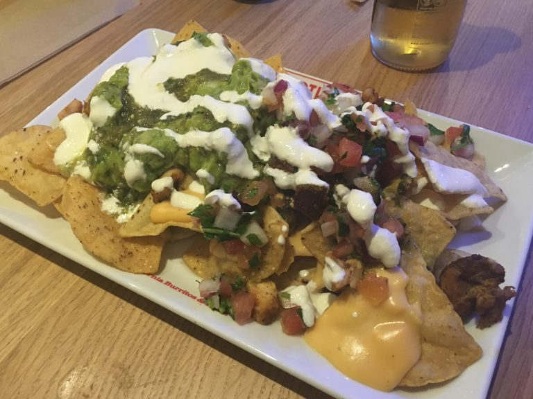 Nachos topped with cheese, guacamole, salsa, jalapenos, soured cream and grilled chicken
