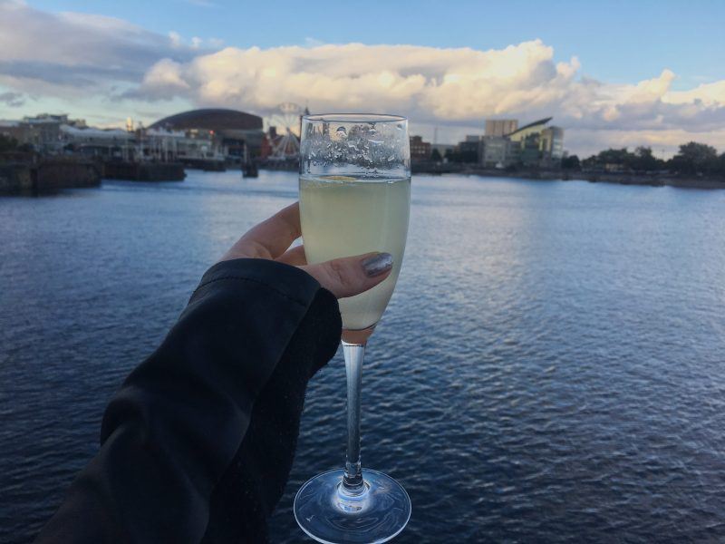 Holding a glass of Prosecco against the backdrop of Cardiff Bay