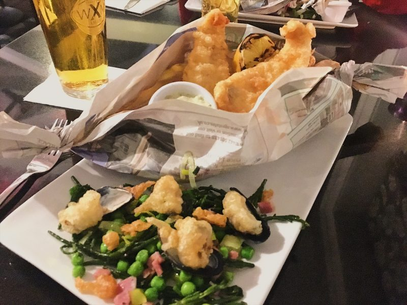 Battered plaice and chips in boat-shaped newspaper wrapping, served with Peas de Gallos