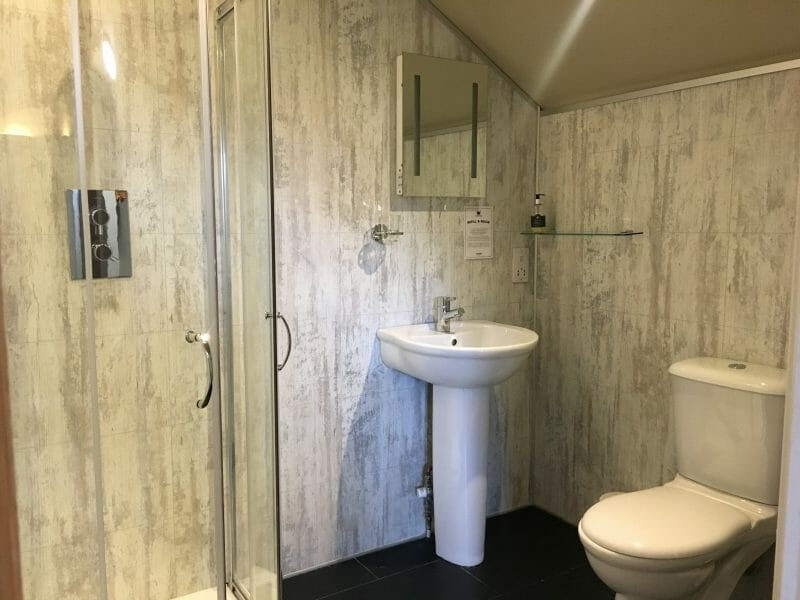 The upstairs bathroom in a Tenby lodge at Bluestone Wales, with a shower cubicle, sink and toilet