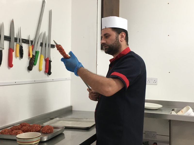 Jihat showing us how to form the mincemeat onto the skewers in making Adana kebabs
