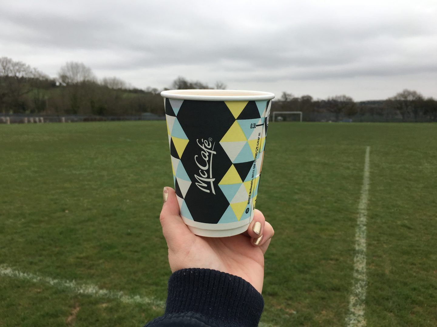 A McDonald's 'McCafe' plastic cup held up in front of a football pitch