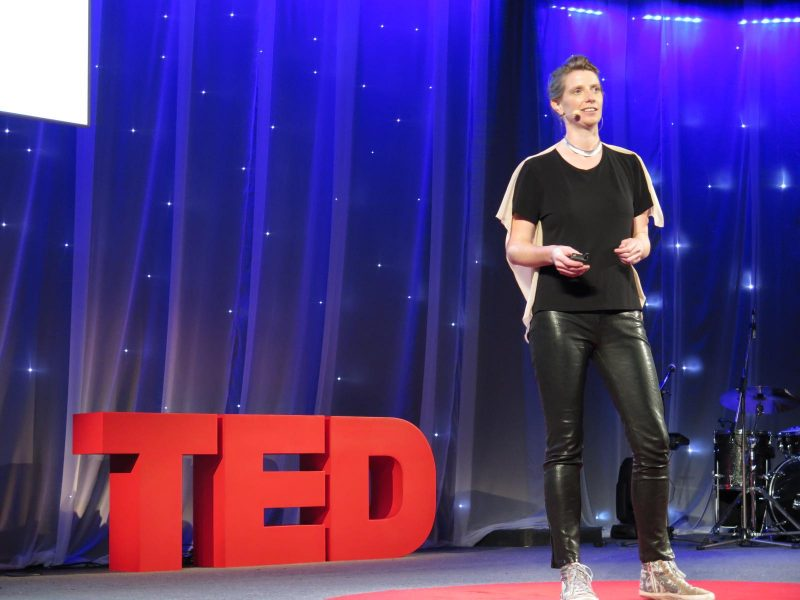 Julie Freeman on stage at a TED talk - a potential way to stay entertained on a long-haul flight