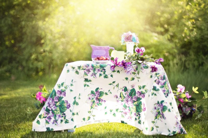 A table dressed in a floral table cloth and laid with crockery, ready for a summer party in the garden