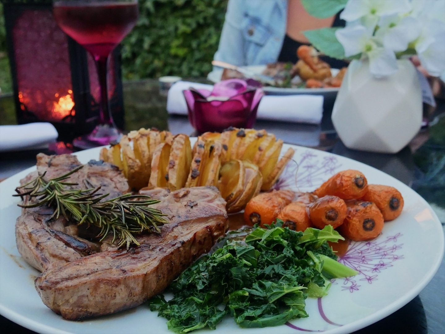 Oak-smoked lamb chops with garlic and rosemary, teamed with kale, roast carrots and Hasselback potatoes - the main course in the Welsh three-course dinner menu