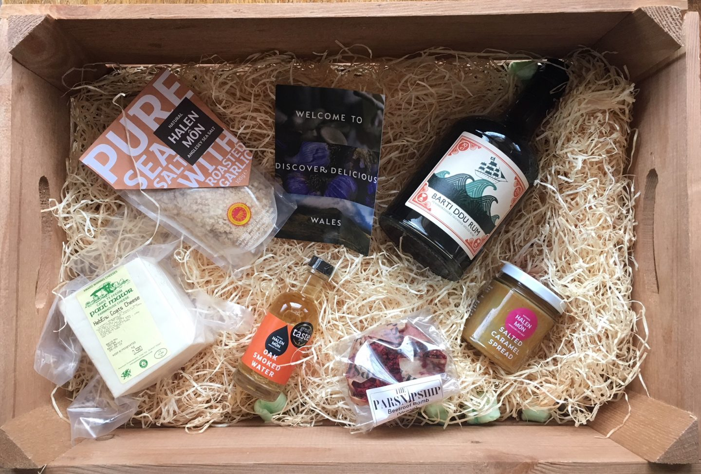 Discover Delicious Wales hamper photographed from above, containing a flat lay of ingredients used to create my Welsh three-course dinner-party menu, on shredded paper