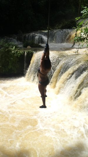 Jumping off a rope swing into a waterfall at YS Falls, Jamaica - backpacking tours are great for adventure, but always allow yourself some rest days to recover.